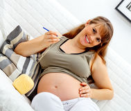 Pregnant female sitting on sofa and knitting Stock Images