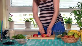 Pregnant female stomach and hands slicing apple fruit on cutting board stock video footage