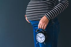 Pregnant female with vintage alarm clock Royalty Free Stock Photography