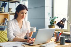 Pregnant business woman working at office motherhood sitting browsing laptop drinking coffee stock photography