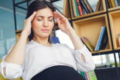 Pregnant business woman working at office motherhood sitting headache royalty free stock photography