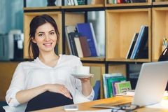Pregnant business woman working at office motherhood sitting holding coffee cup stock photos