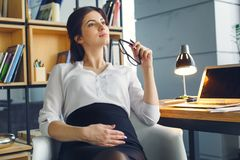 Pregnant business woman working at office motherhood sitting thoughtful stock photo