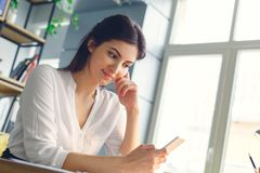 Pregnant business woman working at office motherhood sitting using smartphone royalty free stock image