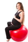 Pregnant fitness woman doing exercise on fitball on white background Stock Image