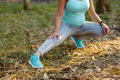 Pregnant fitness woman stretching legs before outdoor workout Stock Images