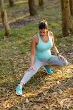 Pregnant fitness woman stretching legs before outdoor workout Royalty Free Stock Images