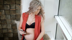 Pregnant future mother in red shirt, blue jeans and black bra sitting on the windowsill with the smartphone. Young stock footage