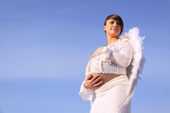 Pregnant girl with angel wings. Pregnant brunette girl embracing a stomach with angel wings on a blue sky background Royalty Free Stock Images
