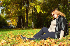 Pregnant girl in the autumn forest. Pregnant girl gently looks at her stomach in the autumn forest Royalty Free Stock Photos