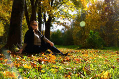 Pregnant girl in the autumn forest. Pregnant girl sits under a tree in autumn Stock Photography