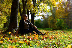 Pregnant girl in the autumn forest. Pregnant girl sits under a tree in autumn Royalty Free Stock Image