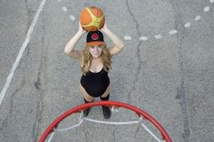 Pregnant girl on the basketball court throws the ball into the ring. view from the top royalty free stock image