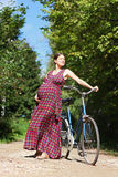 Pregnant girl with bicycle on a forest road, front view Stock Images