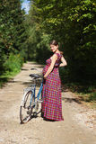 Pregnant girl with bicycle on a forest road, rear view Royalty Free Stock Images