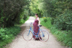 Pregnant girl with bicycle on a forest road, soft focus, side vi Stock Photography