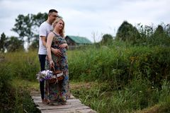 Pregnant girl with big belly and young man outdoor. Pregnant girl with big belly and young men in parkr Stock Image