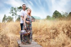 Pregnant girl with big belly and young man outdoor. Pregnant girl with big belly and young men in parkr Royalty Free Stock Image