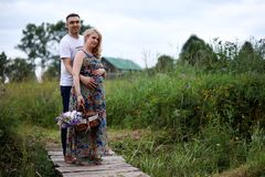 Pregnant girl with big belly and young man outdoor. Pregnant girl with big belly and young men in parkr Stock Photos