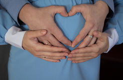 The pregnant girl in a blue dress with heart from hands Royalty Free Stock Photography