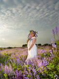 Pregnant girl a bouquet of wild flow. Pregnant girl in a field with a bouquet of wild flowers Stock Photo