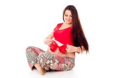 Pregnant girl corrects red bow on her stomach Stock Photos