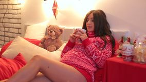 Pregnant girl with a cup of tea on New Year`s Eve. Young pregnant girl in a red knitted sweater lies with a cup of tea on the bed against the backdrop of a stock footage