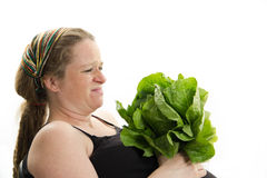 Pregnant girl doesn't like healthy food lettuce isolated Stock Photography