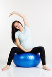 Pregnant girl doing breathing exercises on fitball. Caucasian young woman exercising stretching and yoga for pregnant with blue fitball in studio isolated on Stock Photo