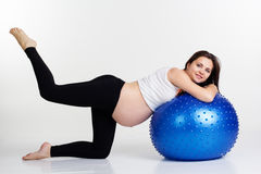 Pregnant girl doing fitness exercises with fitball. Caucasian pretty woman exercising stretching and yoga for pregnant with blue fitball in studio isolated on Royalty Free Stock Image