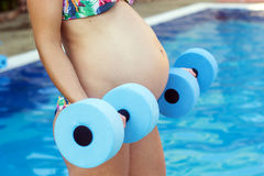 Pregnant girl is doing sport with dumbbells near Stock Photography