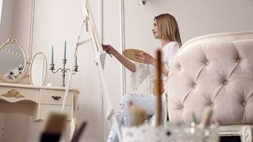 A pregnant girl draws a picture sitting at home on a bed in a bright bedroom. A young pregnant girl draws a picture sitting at home on a bed in a bright bedroom stock footage