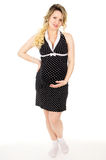Pregnant girl in a dress stands isolated Royalty Free Stock Photo