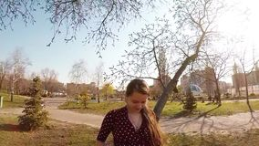 Pregnant girl in a dress is stroking belly under a tree in a spring park. In Kiev stock video