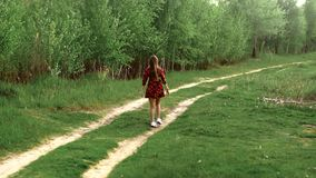 Pregnant girl in dress walks through the wood stock footage