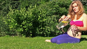Pregnant girl drink water with lemon in park. Healthy pregnancy Stock Images