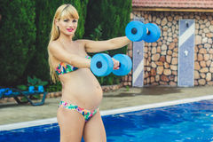 Pregnant girl with dumbbells near swimming pool Royalty Free Stock Images