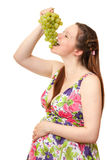 Pregnant girl eating grapes. Royalty Free Stock Photography