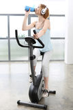 Pregnant girl exercising on a stationary bike Royalty Free Stock Photo