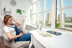 Pregnant girl feeling unwell while sitting in modern apartment. Woman in a state of pregnancy suffering from headache. She sitting near big window in light room stock photos