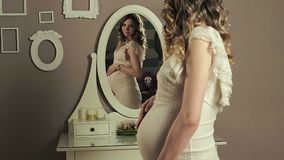 Pregnant girl in front of mirror stock video footage