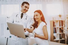 Pregnant Girl at the Gynecologist Doctor. Doctor is a Man. Doctor is Showing Something on Laptop to Woman. Girl is Sitting on Couch and Pointing on Laptop stock photo