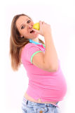 Pregnant Girl healthy food Apple. Cute young pregnant woman with pink green shirt is eating natural food. She has long hair, big baby belly. the huge tummy opens Stock Images
