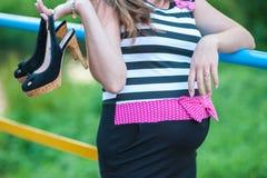 Pregnant girl with heels in her hands. Goodbye heels hello pregnancy stock images