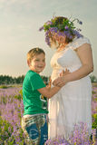 Pregnant girl with her son. The boy hugs his mother`s belly Royalty Free Stock Images