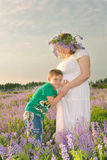 Pregnant girl with her son. The boy leaned his ear against the mother`s stomach Royalty Free Stock Photography