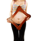 Pregnant girl holding a picture frame on her belly Stock Photography