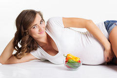 Pregnant girl is holding plate with vegetables Stock Image