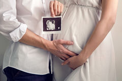 Pregnant girl holding with their hands the belly and the husband keeps the hand in the ultrasound stock photography