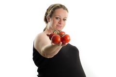 Pregnant girl holding tomatoes in her hand, healthy food isolated Royalty Free Stock Image
